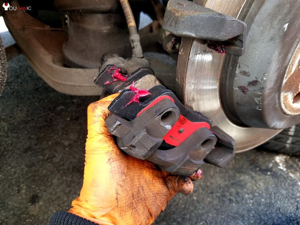 placing new brake pads on rear caliper bracket